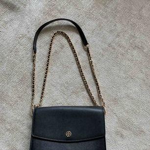 Väska från Tory Burch i mycket bra skick. Använd i ca 2 år. Inköpt på Jackie i Stockholm. Dustbag medföljer! Väskan är svart med gulddetaljer. Vid intresse skickas fler bilder. Bandet går att reglera i två längder.