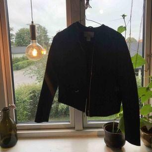 En svart jacka med ett diskret mönster i svart. Två fickor fram och en dragkedja som är svängning.