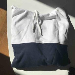 Hoodie med blockfärger i vitt, rött och blått. Ytterst lite smink har kommit vid halsen fram på insidan av hoodien. Använd några gånger men fräsch.