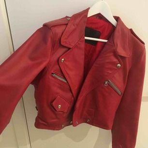 Röd Vintage fake läderjacka med puffiga axlar och smal midja som hår att spänna in. Riktigt cool och man känner sig som en popartist ;) köpt på secondhand men knappt använd
