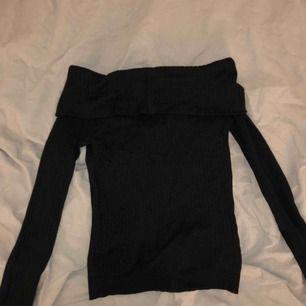 En svart ribbad of shoulder topp som är ganska kort i modellen, knappt använd