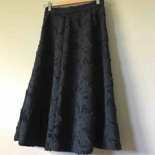 Mörkblå midi kjol med blommönster/applikationer, använd en gång så den är i väldigt bra skick! (Färgen skiftar i ljuset därför ser den blå/svart fläckig ut på bild...) stängs med dragkedja i sidan. 🦋