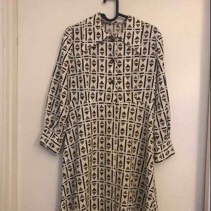 """Vintage. 70tals klänning. Fortfarande i väldigt fint skick. En av knapparna på """"magen"""" hänger löst, men med lite tråd så sitter den igen."""