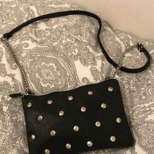 Svart liten väska med nitar på. (18x13cm)