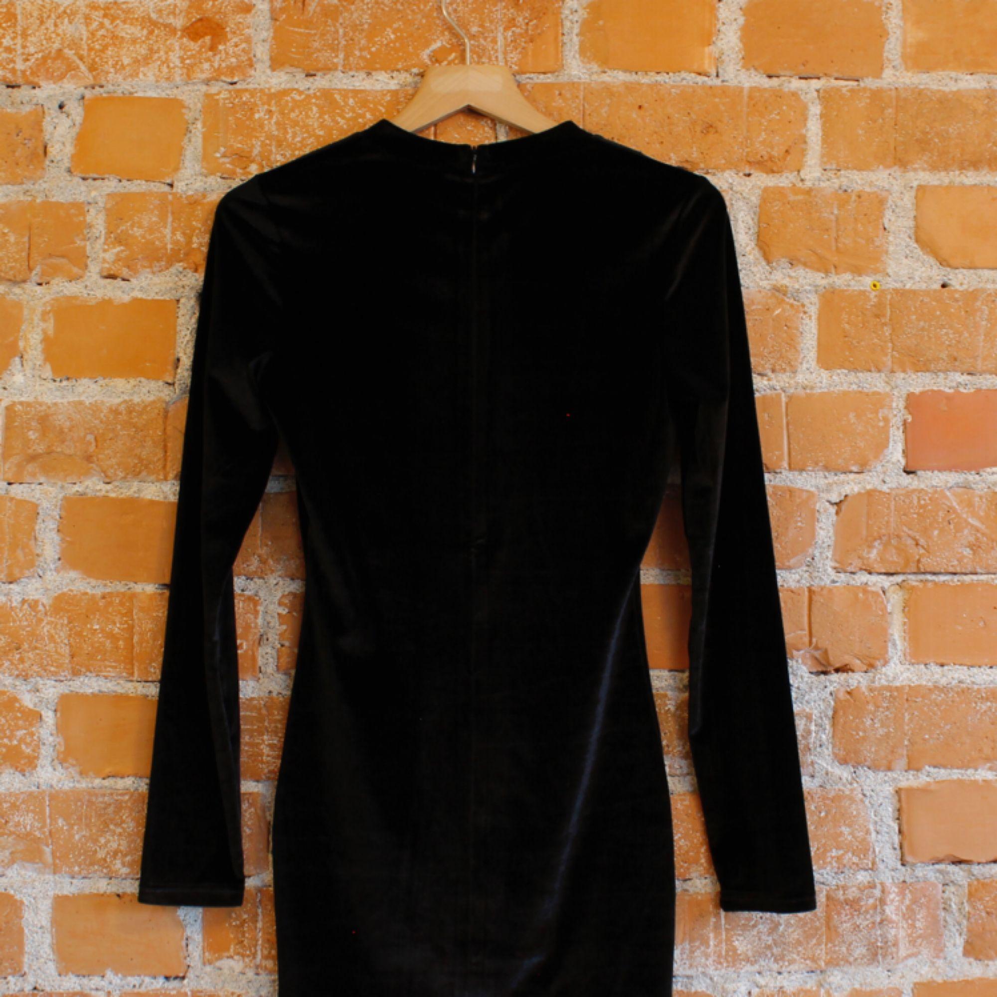 Kort kattklänning i svart sammet, står strl M men skulle säga att den är XS-S Dragkedja i rygg. Klänningar.