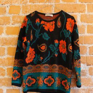 Stickad tröja i strl S med blommor på svart botten. Använt skick