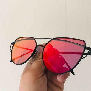 Solglasögon med rosa/rött glas, ej använda. Köparen står för frakt
