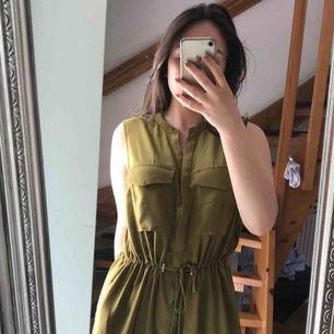 En olivgrön klänning i härligt svalt material i sommarvärmen. Den har ett bälte/justerbar midja. Kan även bäras öppen som en lång väst.