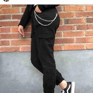 """Svarta """"cargo"""" byxor med tillhörande kedja, använda ett fåtal gånger"""