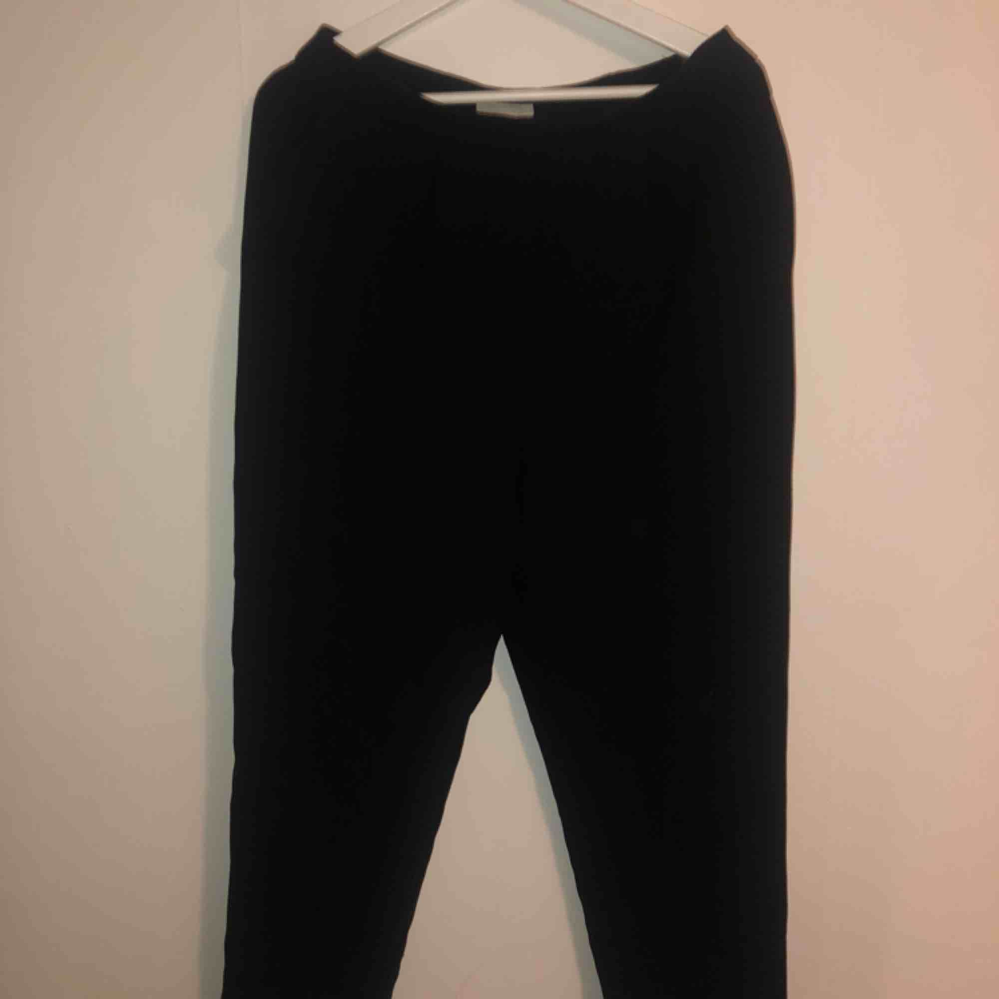 Svarta kostymbyxor med dragkedjan på sidan.. Jeans & Byxor.