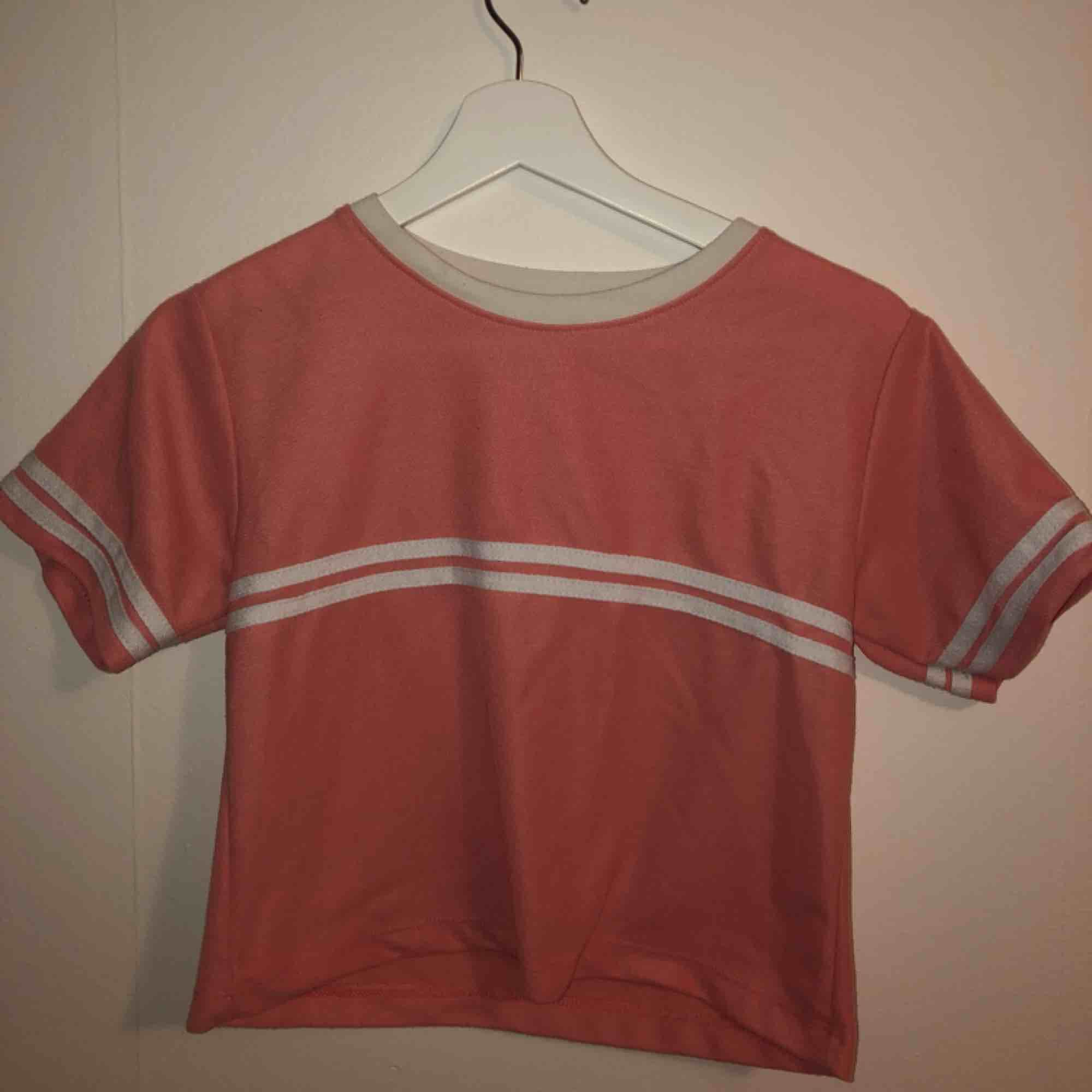 Fin t-shirt i korallrosa färg.. T-shirts.