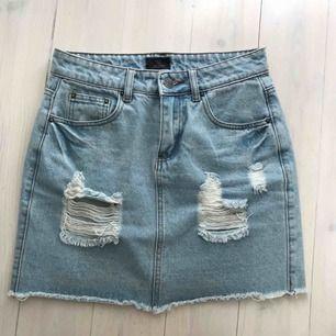 Snygg kort jeanskjol med slitningar. Från Nelly.com och knappt använd. Den perfekta jeanskjolen!
