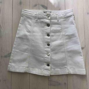 Trendig kort vit jeanskjol. Triangelform med silvriga knappar. Knappt använd👍