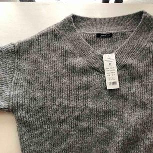 Grå stickad tröja från Gina Tricot. Helt oanvänd, lappen kvar. Ordinarie pris: 399 kr.