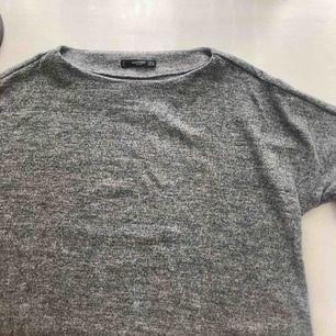 Grå tröja från Mango med utsvängda armar.