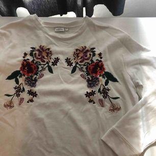 Vit tröja med blommigt mönster.
