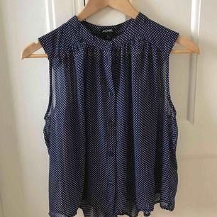 Söt marinblå blus med vita prickar. Aldrig använd med prislapp kvar. Riktigt fin till fest eller vardag!
