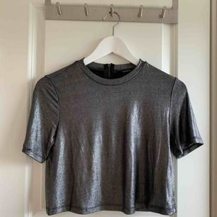 Metallic glittrig/glansig t-shirt från Forever21. Superfin festlig topp, något kortare i modellen, zipper i bak. True to size. Frakt 36kr tillkommer, kolla gärna in mina andra plagg- jag samfraktar gärna! 🌟