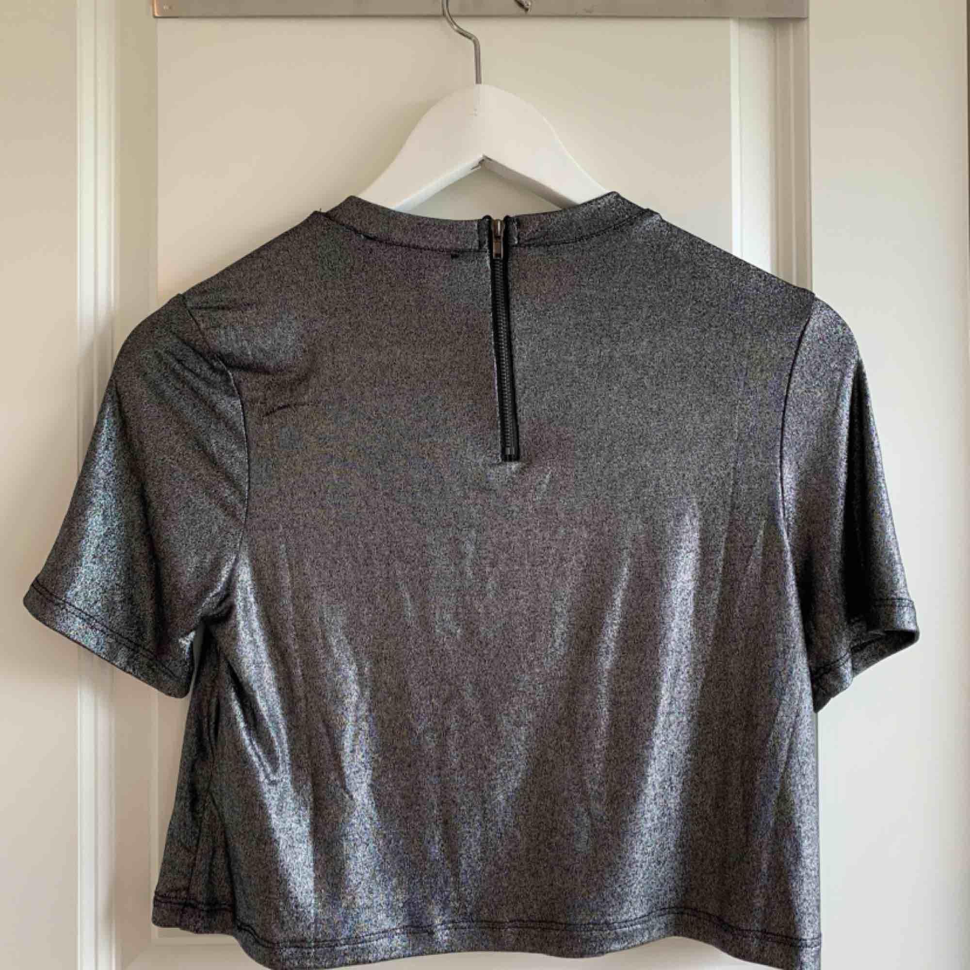 Metallic glittrig/glansig t-shirt från Forever21. Superfin festlig topp, något kortare i modellen, zipper i bak. True to size. Frakt 36kr tillkommer, kolla gärna in mina andra plagg- jag samfraktar gärna! 🌟. T-shirts.