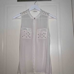 Vit blus/top med knappar framtill & guldnitar vid bröstfickor & axlar, djup urringning i ryggen. Köpt från Vero Moda i storlek XS. Frakt ingår!