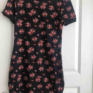 En svart figursydd klänning med röda blommor på. Den är ganska kort och sitter väldigt tight så S-M skulle nog också kunna ha den. Säljer pga att jag inte använder den. Nypris: 199kr men jag säljer för 90kr + frakt och betalningen sker via swish