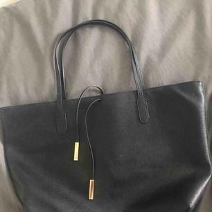 En svart väska från H&M med guldiga detaljer och även 4 innerfack och en dragkedja så man kan stänga den. Säljer pga att jag inte använder den. Nypris: 299kr och jag säljer den för 100kr + frakt och betalningen sker via swish