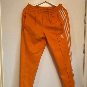 Fräsch orange Adidas tracksuit-byxor i storlek M! Använd 1 gång! Nypris ligger på 700kr. Kan mötas upp eller köra på frakt. Frakt ligger dock på köpare.