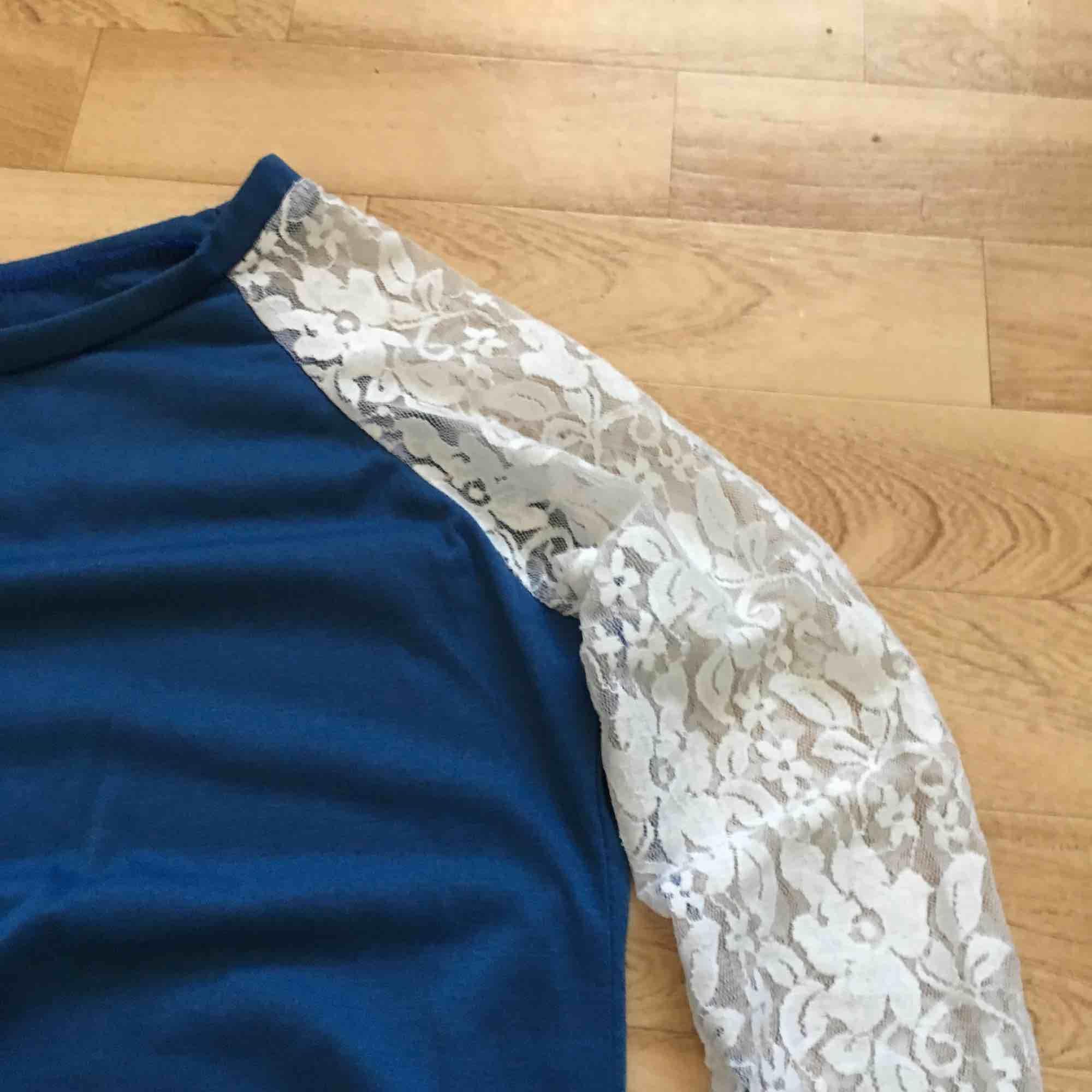Supersöt blå vanlig  tunn longsleeve tröja med okänt ursprung! Passar stl XS även om det inte står något i den. Unik med de vita blomstermash-ärmarna som gör den extra somrig! . Toppar.