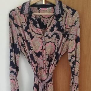Fin rosa/aprikos mönstrad skjortklänning på mörkblå botten i stl L från Indiskan. Obetydligt använd. Djur finns i hemmet.  Kan skickas mot att köparen står för frakten.
