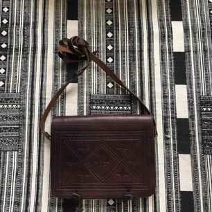 Vacker läderväska inköpt i Essaouira i Marocko. Äkta läder, enkel i sin utformning med två separata fack inuti och tillknäppning i form av små läderknutar på utsidan av locket. Präglat läder och justerbar längd på axelremmen.