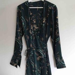 Kimono-klänning i glansigt tunt material. V-ringad med omlottknytning i midjan, lätt utställda ärmar, slutar under knät. Kan användas som klänning eller morgonrock. Frakt tillkommer på 50 kr <33