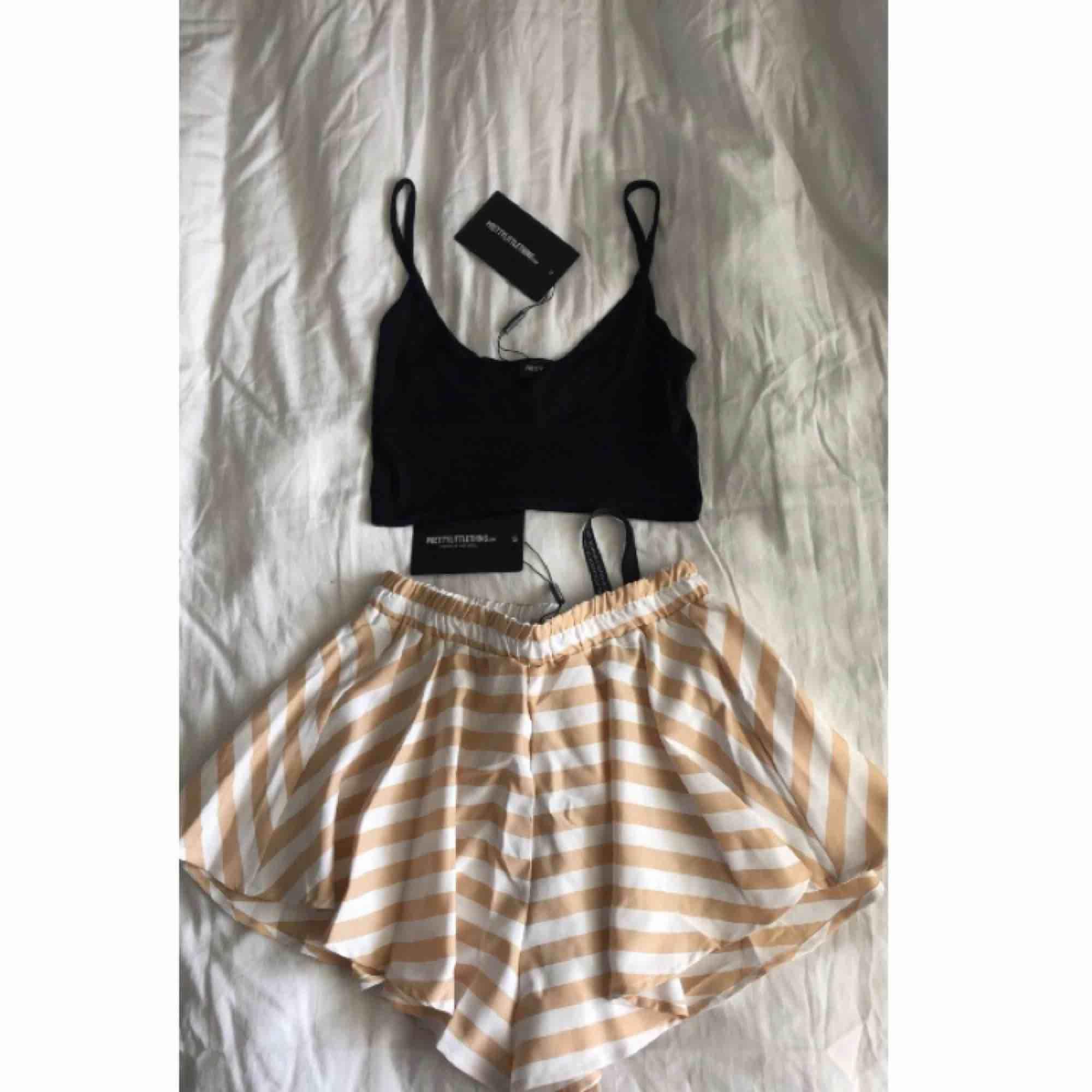 Oanvänd shorts-kjol och linne från pretty little thing, storlek 34 i shortsen men skulle säga de är mer som 36, säljer båda för 100kr eller kjolen för 85kr och linnet för 30kr . Shorts.