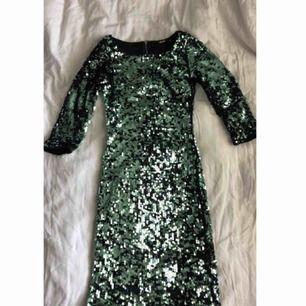 Glittrig kort klänning med trekvartsärm och öppen i ryggen med dragkedja där bak, använde på nyår för några år sen