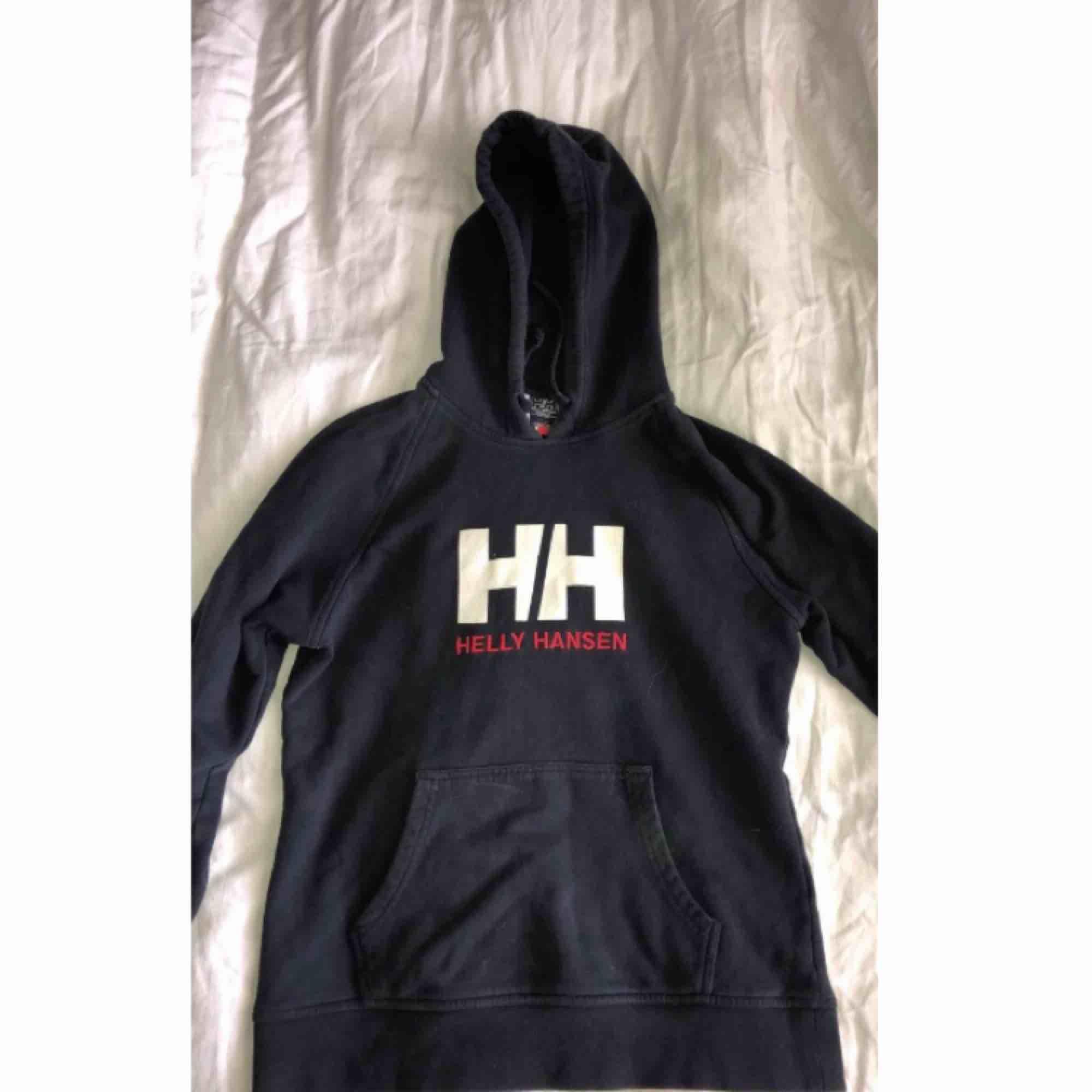 Helly Hansen hoodie i mörkblå, ser urtvättad ut men den ska vara så, fint skick. Huvtröjor & Träningströjor.
