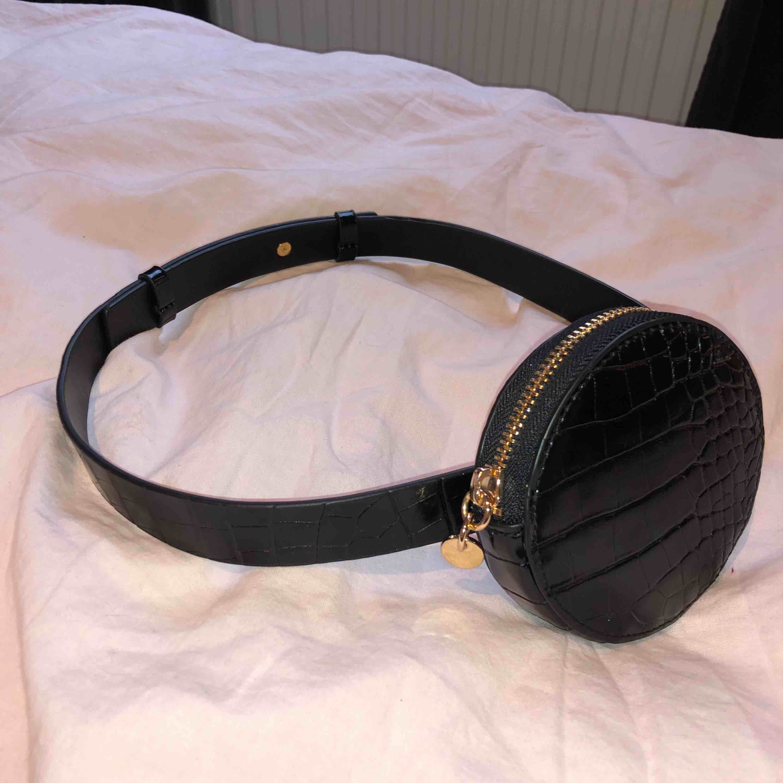 Midjebälte i ormskinn mönster och guldiga detaljer, liten väska (plånbok) och reglering bak. . Accessoarer.