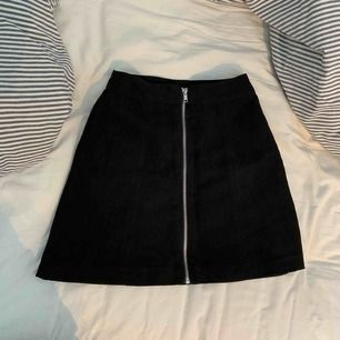 En supersnygg svart mocka-imitation kjol från H&M, storlek 32. Aldrig använd, säljer pga för liten för mig :( Köparen står för frakt!