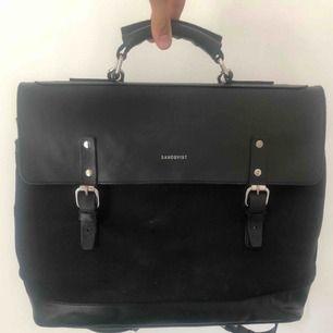 """Multifunktionell väska i bomullscanvas och läder.  Får plats med dem flesta 15"""" laptops.   Väskan är använd i ett par år och har lite slitage på ena remmen, därav det låga priset, men i övrigt väldigt fint skick."""