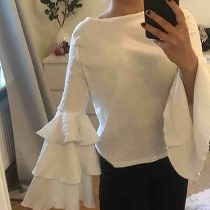 Fin vit blus med volanger på ärmarna, ser lyxig ut, använd 1 gång
