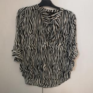 Oanvänd tunn skjorta i zebra mönster. Säljes endast då den aldrig kommit till användning.