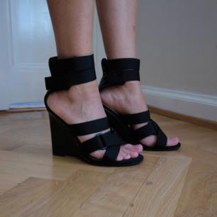 Unika sportiga sandaletter från H&M Studio runway SS17 med hög kilklack. Skorna bars av Gigi Hadid under visningen! Sandaletterna har remmar i nylon som stängs med kardborre och innersula i läder. Något slitna bak på hälen (se bild), annars fint skick.