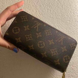 """En fake Louis Vuitton plånbok med två stora """"synliga"""" fack och där inuti flertal mindre fack! Fint skick, köpt på Humana för ca 2 år sedan men jag själv har aldrig använt den!"""
