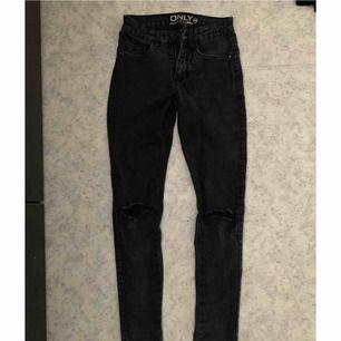 Ett par mörkgråa jeans med hål i knäna,   köpta ifrån Nelly.  Storlek XS