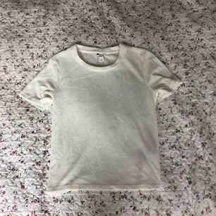 Vit lite finare t-shirt i räfflat tyg. Från Monki. Tunnare material, perfekt för sommaren. Krämig vit. Passar S och M. Frakt tillkommer.