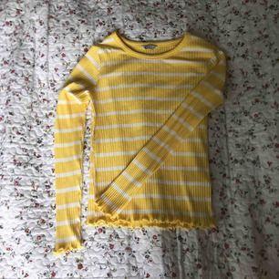 Tight randig långärmad i gult och vitt. Använd väldigt få gånger. Fina små volanger vid ärmarna och i slutet på tröjan. Frakt tillkommer.