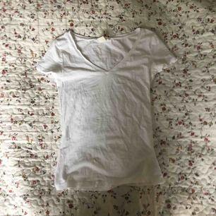 Väldigt tight v-ringad t-shirt i vitt från H&M. Litet hål vid ena ärmen. Lite genomskinlig. Frakt tillkommer.