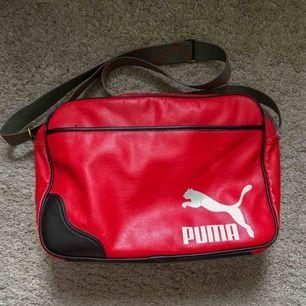 En retro puma väska. Röd med detaljer i militärgrön och bromsguld. Perfekt att ha som gymväska eller att använda vardagligt. Fint skick bortsett från lite bortskavd färg. Kan frakta eller mötas upp i Stockholmsområdet.