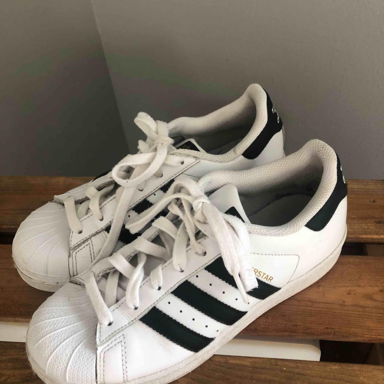 Säljer ett par äkta Adidas superstar. Förutom skadan på bilden så ser dem ut som nya. Storlek 37-38. Frakt tillkommer!. Skor.