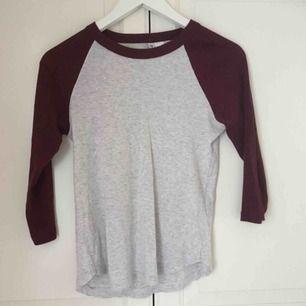 Ljusgrå och vinröd tröja från H&M. Liten i storleken och croppad modell, okej skick. Väl använd!