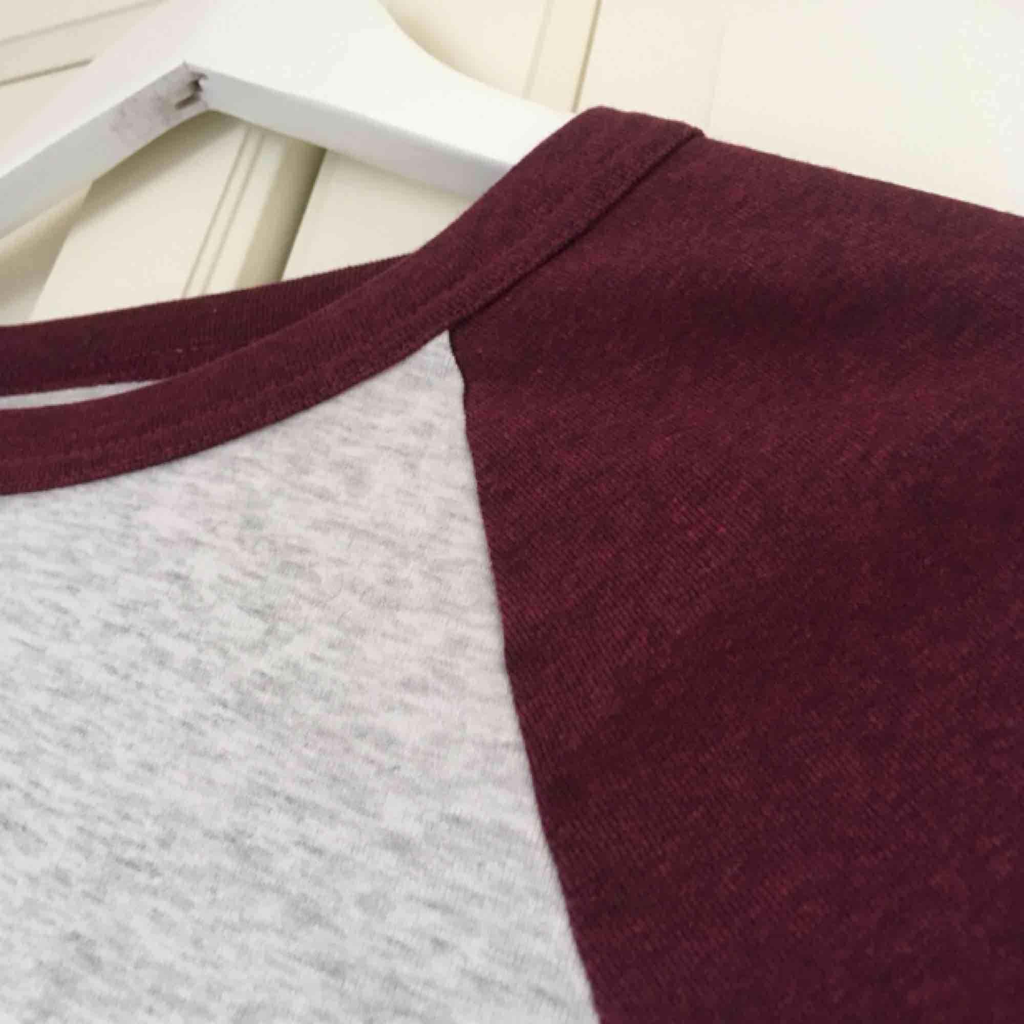 Ljusgrå och vinröd tröja från H&M. Liten i storleken och croppad modell, okej skick. Väl använd!. Toppar.