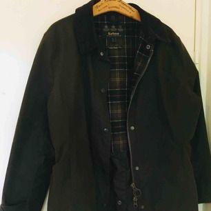 Vaxad jacka med rymlig passform från Barbour Lifestyle. Varumärkets klassiska vaxade modell Beaufort som tillverkats sedan 1983, designad av Dame Margaret Barbour. • Tillverkad i England. • Använts av min mamma ca 2 gånger